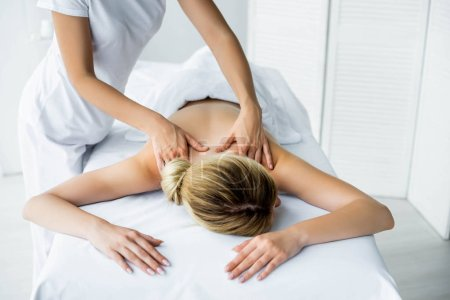 Photo for Cropped view of masseur doing back massage to woman in spa - Royalty Free Image