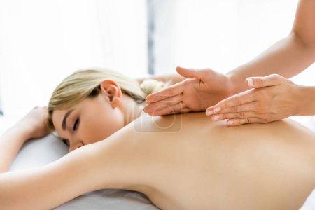 vista recortada de masajista haciendo masaje de espalda a mujer atractiva en spa