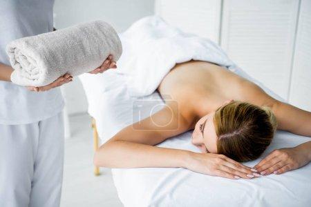 Photo pour Vue raccourcie de la serviette de fixation de masseur et de la femme se trouvant sur le tapis de massage - image libre de droit