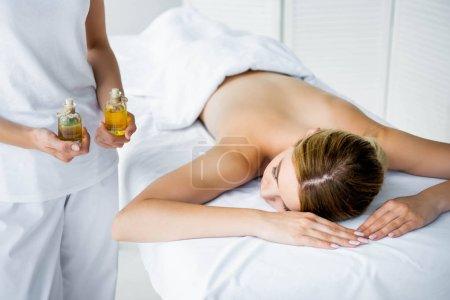 Photo pour Vue recadrée des huiles de parfum de fixation de masseur et femme se trouvant sur le tapis de massage - image libre de droit