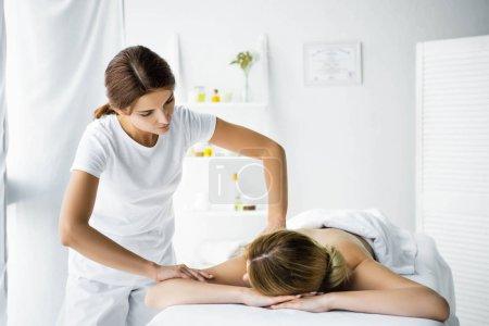 Photo pour Masseur attrayant faisant le massage de dos à la femme dans le spa - image libre de droit