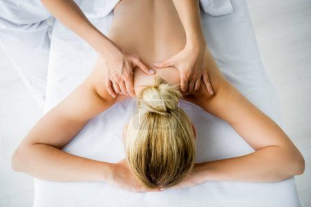 Photo pour Vue recadrée de masseur faisant le massage de dos à la femme dans le spa - image libre de droit