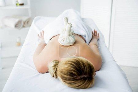 Photo pour Femme couchée sur tapis de massage avec des boules à base de plantes sur le dos - image libre de droit