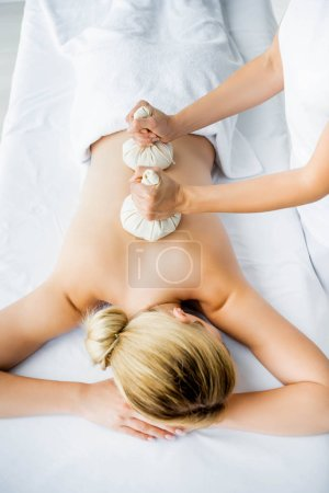 Photo pour Vue recadrée de masseur faisant le massage de dos avec des boules de fines herbes à la femme dans le spa - image libre de droit