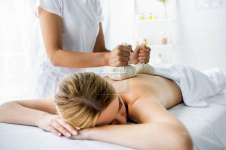 Photo pour Vue recadrée de masseur faisant massage du dos avec des boules à base de plantes à la femme dans le spa - image libre de droit