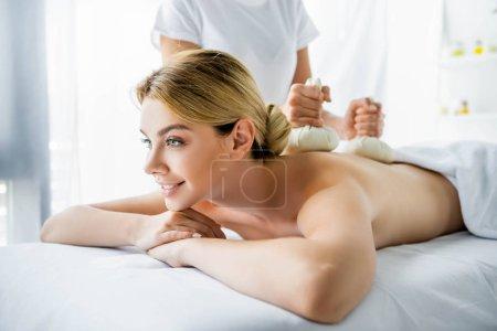 Photo pour Vue recadrée de masseur faisant le massage de dos avec des boules de fines herbes à la femme de sourire dans le spa - image libre de droit