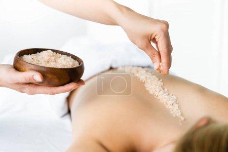 Photo pour Vue recadrée du masseur appliquant du sel de mer sur le dos de la femme - image libre de droit