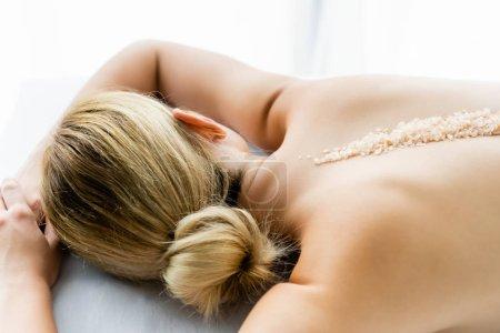 Photo pour Femme se trouvant sur le tapis de massage avec le sel de mer sur le dos - image libre de droit