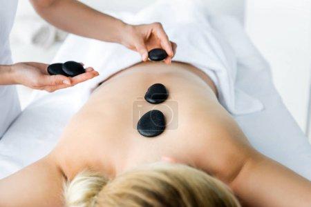 Photo pour Vue recadrée du masseur faisant massage aux pierres chaudes à la femme dans le spa - image libre de droit