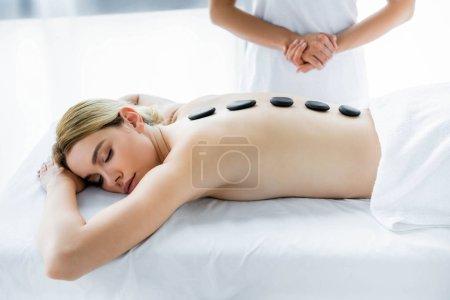 Photo pour Vue recadrée du masseur faisant le massage chaud de pierre à la femme dans le spa - image libre de droit