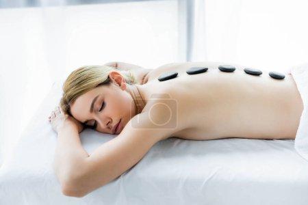 Photo pour Femme attirante avec des pierres chaudes sur le dos se trouvant sur le tapis de massage - image libre de droit