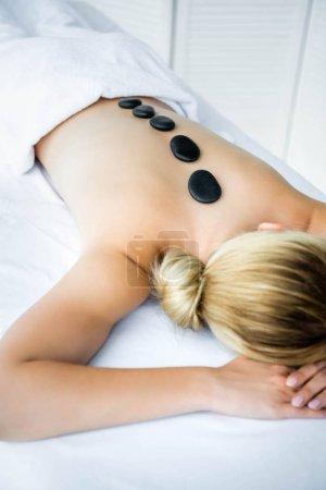 Photo pour Femme avec des pierres chaudes sur le dos se trouvant sur le tapis de massage - image libre de droit