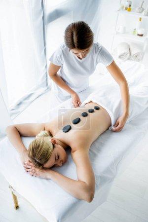 Photo pour Vue d'angle élevé du masseur faisant le massage chaud de pierre à la femme dans le spa - image libre de droit