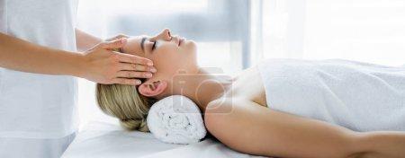 Photo pour Plan panoramique de masseur faisant massage du visage à la femme attrayante - image libre de droit
