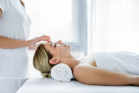 Photo pour Vue recadrée de masseur faisant le massage de visage à la femme attirante - image libre de droit