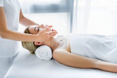 Photo pour Vue recadrée de masseur faisant massage du visage à la femme attrayante - image libre de droit