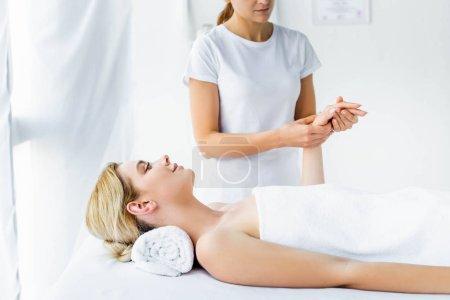 Photo pour Vue recadrée de masseur faisant massage des mains à la femme attrayante - image libre de droit