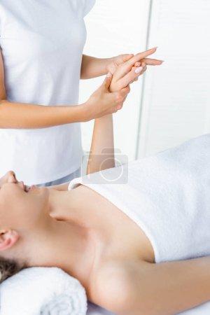 Photo pour Vue recadrée de masseur faisant le massage de main à la femme de sourire - image libre de droit