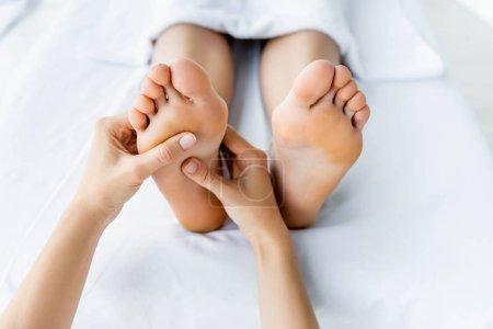 Photo pour Vue recadrée de masseur faisant le massage de pied à la femme dans le spa - image libre de droit