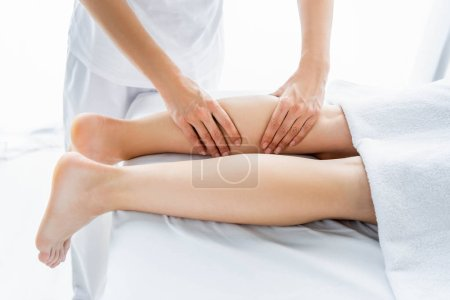 Photo for Cropped view of masseur doing foot massage to woman in spa - Royalty Free Image