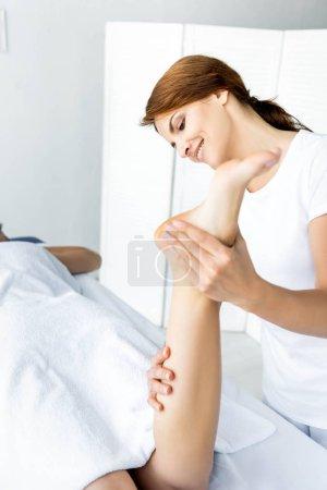 Photo pour Masseur attrayant et souriant faisant le massage de pied à la femme dans le spa - image libre de droit