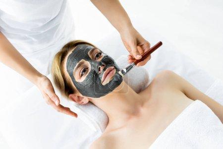 Photo pour Vue recadrée de l'esthéticienne appliquant masque d'argile sur le visage de la femme - image libre de droit