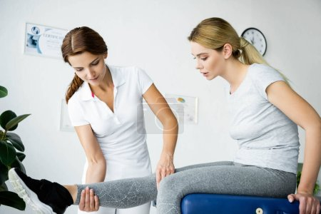 Foto de Quiropráctico tocando la pierna del paciente atractivo en la camiseta gris - Imagen libre de derechos