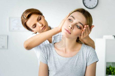 Foto de Quiropráctico tocando la cabeza de paciente atractivo en camiseta gris - Imagen libre de derechos