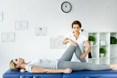 Photo for Chiropractor touching leg of attractive patient in grey t-shirt - Royalty Free Image