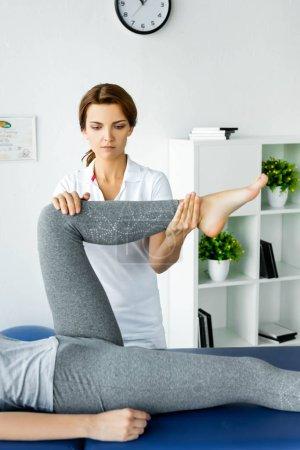 Photo pour Vue recadrée du chiropraticien touchant la jambe du patient dans les leggings gris - image libre de droit