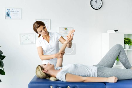 Photo for Chiropractor touching hand of attractive patient in grey t-shirt - Royalty Free Image
