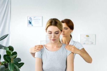 Photo pour Chiropracteur touchant les épaules d'un patient séduisant en t-shirt gris - image libre de droit