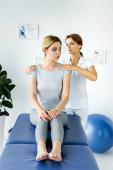"""Постер, картина, фотообои """"мануальный терапевт трогательно плечи привлекательного пациента в серой футболке"""""""