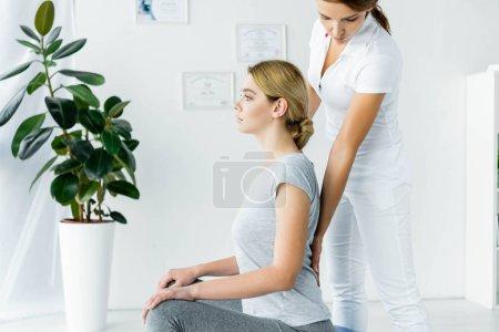 Photo pour Vue latérale du patient attrayant assis et chiropraticien touchant son dos - image libre de droit