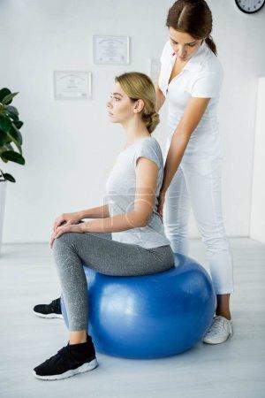 Photo pour Patient attrayant s'asseyant sur la bille bleue d'exercice et le chiropraticien touchant son dos - image libre de droit
