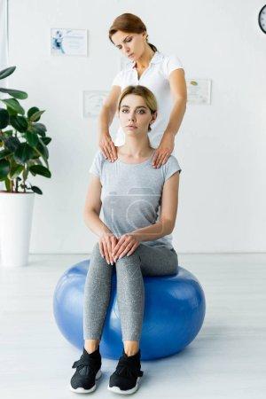 Photo pour Patient attrayant s'asseyant sur la boule bleue d'exercice et le chiropraticien touchant ses épaules - image libre de droit