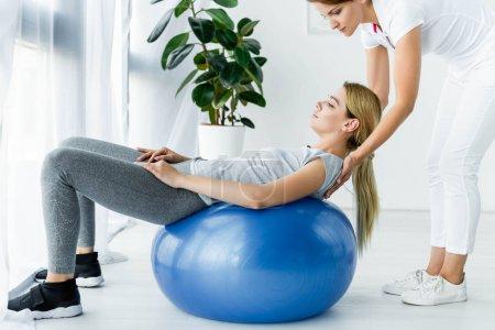 Photo pour Patient attirant se trouvant sur la boule bleue d'exercice et le chiropraticien touchant ses épaules - image libre de droit