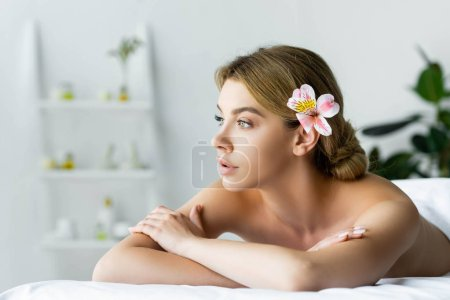 Photo for Attractive woman with flower lying on massage mat in spa - Royalty Free Image