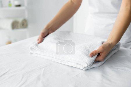 Photo pour Vue recadrée du masseur tenant une serviette blanche au spa - image libre de droit