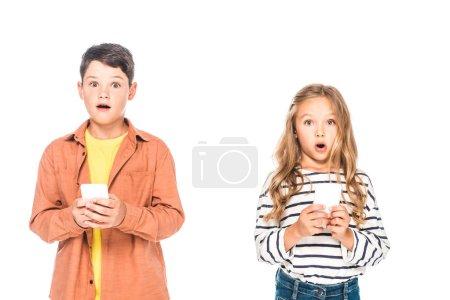 Photo pour Vue de face des enfants choqués à l'aide de smartphones isolés sur blanc - image libre de droit