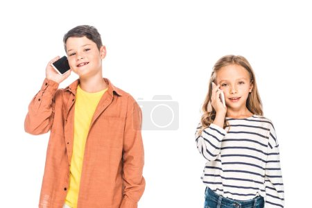 Photo for Two smiling kids talking on smartphones isolated on white - Royalty Free Image