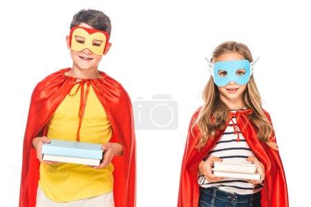 Photo pour Vue avant de deux gosses de sourire dans des masques et des manteaux de héros retenant des livres d'isolement sur le blanc - image libre de droit