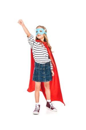 Photo pour Vue pleine longueur de l'enfant dans le masque et le manteau de héros tenant le poing isolé sur blanc - image libre de droit