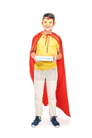 Photo for Full length view of kid in mask and hero cloak holding books on white - Royalty Free Image