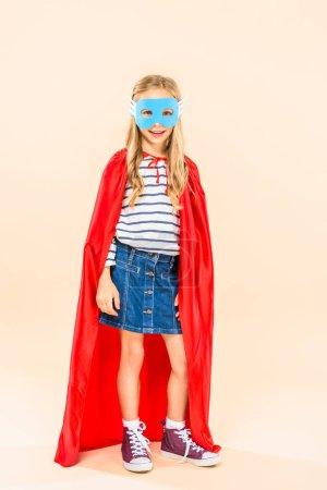 Ganzkörperansicht des lächelnden Kindes in Maske und Heldenmantel auf rosa