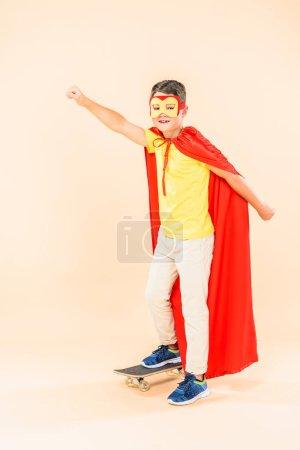 Photo pour Vue pleine longueur de l'enfant dans le masque et le manteau de héros tenant le poing vers le haut tout en se tenant dans la planche à roulettes sur rose - image libre de droit