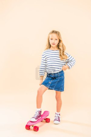 full length view of child standing on skateboard with hand on hip on pink