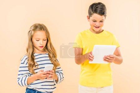 Foto de Dos niños usando teléfono inteligente y tableta digital aislado en rosa - Imagen libre de derechos