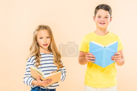 Photo for Front view of  two smiling kids holding books isolated on pink - Royalty Free Image