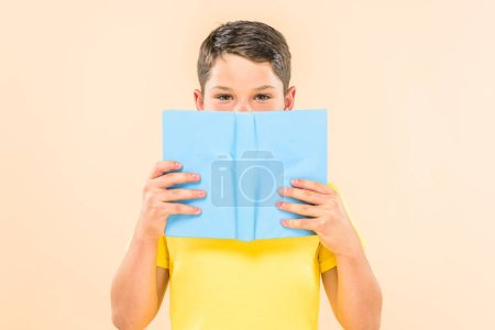 Photo for Front view of boy in yellow t-shirt holding book isolated on pink - Royalty Free Image
